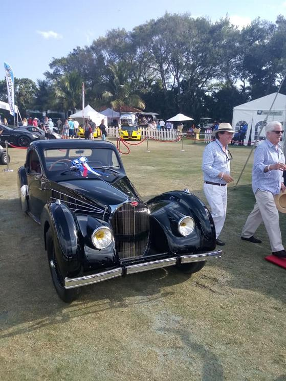 guy in panama hat walking by the classic bugatti at 2019 Boca Raton Concours d'Elegance